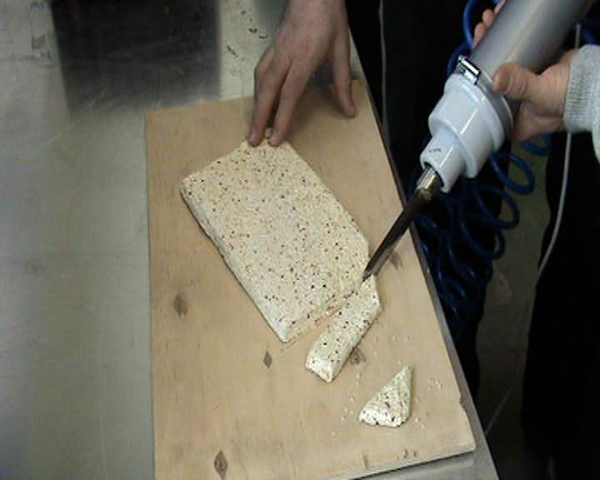 Cutting of nougat with nuts by hand ultrasonic knife